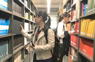 図書館で本を探す生徒二人。