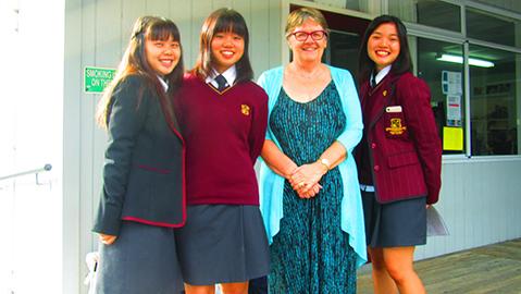 海外で、現地先生と一緒に笑顔の佼成学園女子生徒