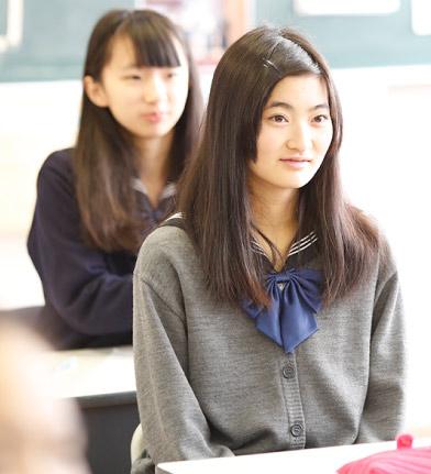 教室で座って、前を向いている女子生徒